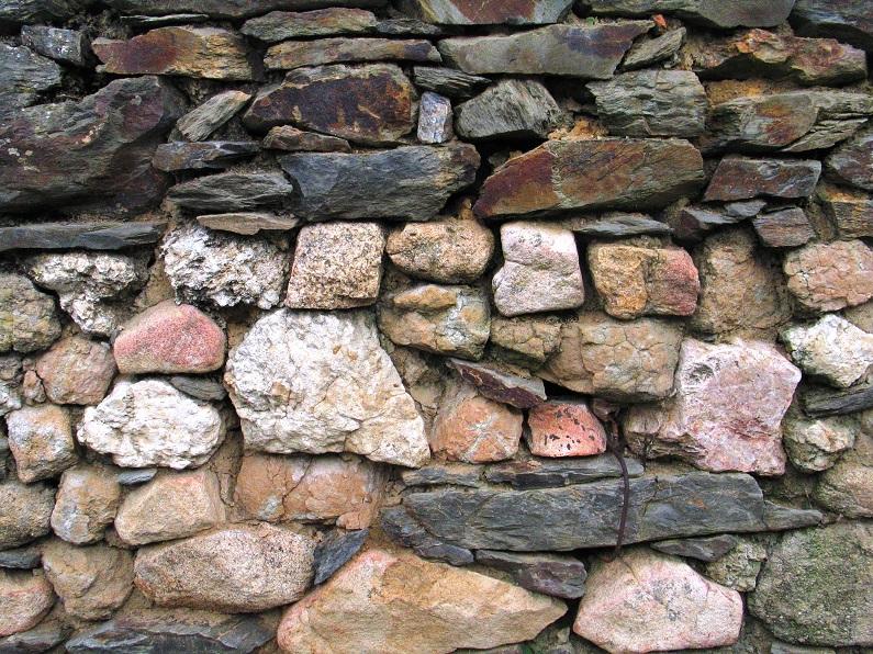 Muro com pedras ligadas por argamassa. Note-se a diversidade da litologia e a dimensão e forma dos vários elementos, cuja disparidade motiva a utilização da argamassa como forma eficaz de manter a estrutura